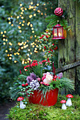 Festive arrangement in red and green with roses and fly agaric mushroom ornaments