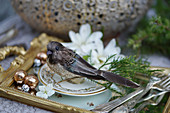 Bird ornament and vintage-style cutlery on gilt tray