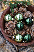 Green baubles and larch cones in bowl