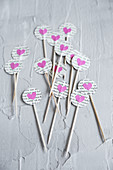 Toothpicks decorated with circles of book pages and pink paper hearts