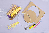 Craft utensils for making lion's head: metal ring, raffia and cardboard