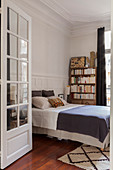 View into bedroom with double bed and bookcase