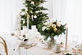 Weihnachtliche Tafel in Cremefarben mit Blumenstrauß und Gastgeschenken