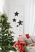 Decorated Christmas tree and paper stars on white wooden panel
