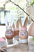 Mit Gesicht bemalte Ostereier mit Hasenohren aus Papier