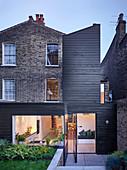 Backsteinhaus mit modernem holzverkleidetem Anbau und Schwenktüren zum Garten