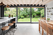 Modern kitchen-dining room with glass wall overlooking garden