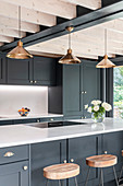 Barstools at counter in modern kitchen with grey cabinets