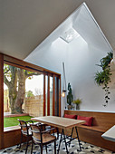 Dining table below light shaft and next to large window overlooking garden