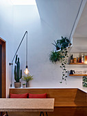 Dining table, bench and houseplants below light shaft