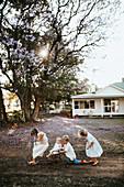 Kinder in weißer Kleidung spielen vor einem Haus auf dem Lande