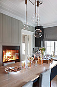 Pendant lamps with spherical glass shades above dining table in front of fire burning in fireplace