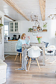 Frau sitzt am Holztisch im Esszimmer im modernen Landhausstil