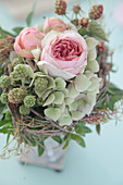 Flower arrangement of roses, hydrangeas and unripe blackberries with collar of twigs