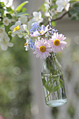 Bouquet with daisies, Blue-eyed-mary, and buttercups hung in a bottle