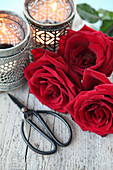 Red roses, scissors and tealights