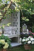 Arbour bench hidden in garden with hydrangeas planted in baskets