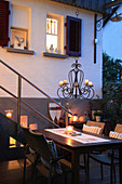 Table and chairs with tealights and candle chandelier on twilight terrace
