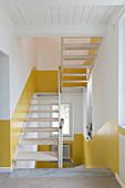 Weißes Treppenhaus mit halbhoch gelb gestrichener Wand