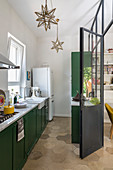 Narrow kitchen with dark green cabinets and honeycomb floor tiles