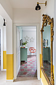 Antique gilt-framed mirror in hallway with yellow painted dado