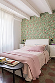 Bed against vintage-style floral wallpaper in bedroom with ceiling beams
