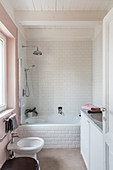 Bathtub clad with subway tiles in small bathroom with pink wall