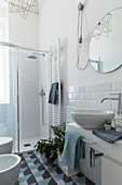 Modern bathroom with subway tiles and graphic pattern on floor