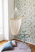 Hanging chair and side table in front of vintage-style floral wallpaper