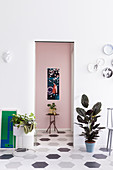 Houseplants flanking doorway leading into hallway with pink wall