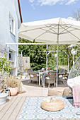 Rattan armchairs below parasol on terrace in spring