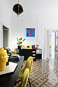 Yellow chairs around dining table in living room with tiled floor