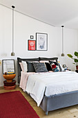 Bedroom with pendant lamps hung from sloping ceiling above bed