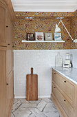 Modern kitchen with wooden cabinets and floating shelf on floral wallpaper