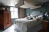 Double bed with canopy and wooden wardrobe in rustic bedroom