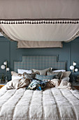 Double bed with canopy against blue wall in rustic bedroom