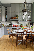 Grey kitchen cabinets and dining table in kitchen with high ceiling