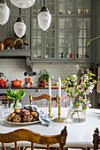 Biscuits and vase of flowering branches on dining table