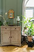 Anrichte mit Vase, Kerzen und Petroleumlampe vor grüner Wand