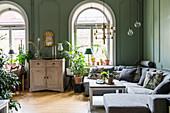 Anrichte, graue Polstergarnitur, Zimmerpflanzen vor Rundbogenfenster im Wohnzimmer mit grünen Wänden