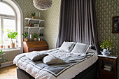 Double bed with canopy in bedroom with patterned wallpaper