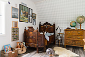 Antique bed and chest of drawers below paintings on wall in child's bedroom