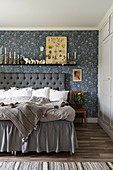 Double bed with button-tufted headboard and blue-patterned wallpaper in bedroom