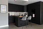 Fitted kitchen with island counter in dark charcoal grey