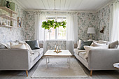 Pale sofas in living room with floral wallpaper
