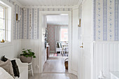 Foyer with white wainscoting and pretty wallpaper