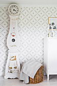 Antique longcase clock against patterned wallpaper