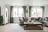 Sofas, coffee table and patterned wallpaper in bright living room