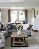 Sofas, coffee table with antique wooden trough and patterned wallpaper in bright living room