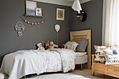 Bett mit Kopfteil aus Holz im Kinderzimmer mit dunkler Wandfarbe